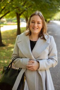 Becky Smith, author of this blog post, standing by a tree in a light tan grey coat.