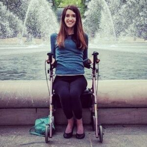 Megan McNally in front of a fountain sitting in a wheel chair. She is wearing a blue shirt, black leggings, and black flat shoes.